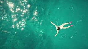 Воздушный верхней части взгляд вниз красивого заплывания молодой женщины в море Стоковое Фото