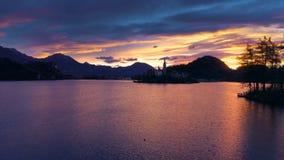 Воздушный взгляд захода солнца церков предположения в озере кровоточил, Словения видео сток-видео