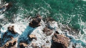 Воздушный взгляд сверху голубых океанских волн ударяя скалистый seashore создавая белую пену и брызгать Волны моря рушась с утеса акции видеоматериалы