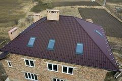 Воздушный взгляд сверху построения крутой коричневой крыши гонта, каминов кирпича и небольших окон чердака на верхней части дома  стоковая фотография rf