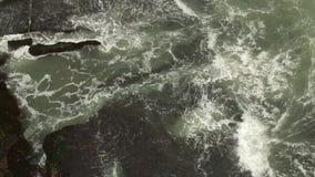 Воздушный взгляд сверху развевает перерыв на темных утесах около пляжа Волны моря на опасном трутне HD вида с воздуха камней снял видеоматериал