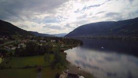 Воздушный взгляд трутня австрийских шлюпки моря Ossiacher озера и городка Ossiach Филлаха гор леса сток-видео