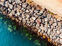 Воздушный взгляд трутня больших утесов и отмелой воды бирюзы моря с рыбной ловлей рыболова на утесах Стоковое фото RF
