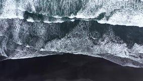Воздушный взгляд трутня волн спеша к берегу на черном вулканическом песке Атлантический океан, Исландия сток-видео