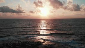 Воздушный взгляд трутня красивого розового захода солнца с sunroad и исполинских океанских волн с великолепным облачным небом на  акции видеоматериалы