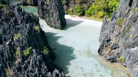 Воздушный взгляд трутня над ясной мелкой водой лагуны окруженной острыми скалистыми образованиями Спрятанный пляж, El Nido Palawa сток-видео
