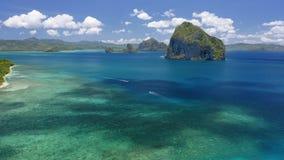 Воздушный взгляд трутня острова Pinagbuyutan с тенями облака двигая дальше поверхность океана Шлюпки banca отключения в море El N сток-видео