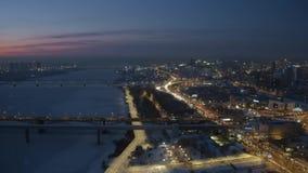 Воздушный взгляд трутня речного берега покрытого снегом города ночи с заторами движения видеоматериал