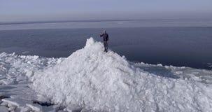 Воздушный взгляд dron молодого активного счастливого человека оставаясь на ледниках льда около береговой линии моря зимы тряся ру акции видеоматериалы