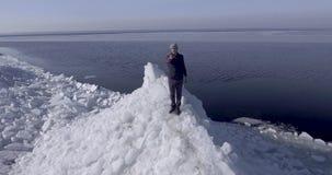 Воздушный взгляд dron молодого активного счастливого человека оставаясь на ледниках льда около береговой линии моря зимы Трутень  акции видеоматериалы