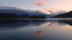 Воздушный вид на озеро трутня кровоточенный с церковью St Marys предположения на небольшом острове; Кровоточенный, Словения, Евро сток-видео