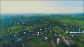 Воздушный запачканный отснятый видеоматериал идя над домами летом 4K
