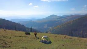 Воздушный - летание вокруг туриста с рюкзаком и шатром на горных склонах сток-видео