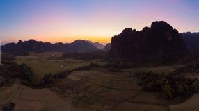 Воздушный: Назначение перемещения backpacker Vang Vieng в Лаосе, Азии Заход солнца над сценарными скалами и башенками утеса, доли стоковая фотография