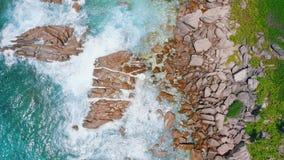 воздушный отснятый видеоматериал взгляда глаза птицы 4k ударять волн брызнул утесы гранита береговой линии на острове Digue Ла, С видеоматериал