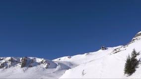 Воздушный отснятый видеоматериал замедленного движения над снежной долиной гребня горы на голубом небе