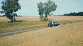 Воздушный отснятый видеоматериал трутня автомобиля на поле, трутень гонит автомобиль сток-видео
