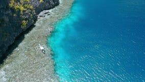 Воздушный отснятый видеоматериал шлюпок banca отключения туристских отдыхая над коралловым рифом около святыни Matinlok El Nido,  видеоматериал