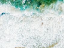 Воздушный панорамный взгляд трутня голубых океанских волн задавливая на песчаном пляже Стоковое Фото
