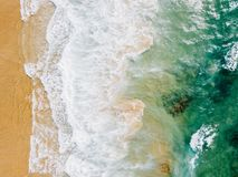 Воздушный панорамный взгляд трутня голубых океанских волн задавливая на песчаном пляже Стоковая Фотография RF