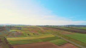 Воздушный полет над дорогой между полями, там blick радуги на начале отснятого видеоматериала и голубое небо полно