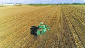 Воздушный трутень снял жатки зернокомбайна работая в поле на заходе солнца сток-видео