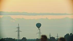 Воздушный шар летая над полем используя технологию жары - башнями связи, башнями антенны - вечер сток-видео