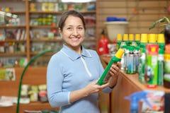 Возмужалая женщина выбирает удобрения на магазине стоковая фотография