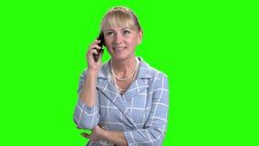 Возмужалая женщина говоря на мобильном телефоне видеоматериал
