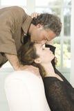 Возмужалые пары целуя в живущей комнате. Стоковые Фото