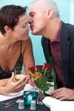Возмужалый поцелуй ресторана пар Стоковые Изображения
