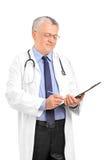Возмужалый профессионал медицинского соревнования писать вниз примечания Стоковое фото RF