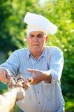 Возмужалым кавказским kebabs shish человека зажженные удерживанием Стоковое Фото