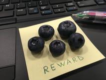 Вознаграждение - рукописное на пост-оно, на клавиатуре компьютера стоковые фотографии rf