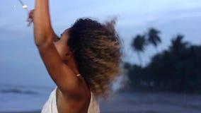 Воздетая красивая женщина держа бенгальский огонь празднуя и скача на пляж в замедленном движении сток-видео