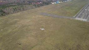 Воздушная съемка малого воздушного судна пропеллера летая около взлётно-посадочная дорожка авиапорта города на солнечный день Стоковые Изображения
