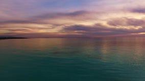 Воздушная съемка, неимоверно красивый штиль на море в свете захода солнца с сериями облаков видеоматериал