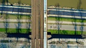 Воздушная съемка пассажирского поезда двигая дальше железнодорожный мост через дорогу реки и велосипеда, взгляд сверху экологичес Стоковое Фото