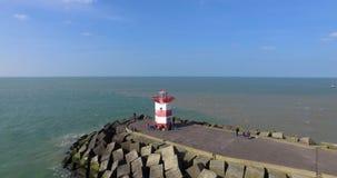 Воздушная съемка Северного моря с маяком и пристанью Летание трутня над морем в Гааге сток-видео