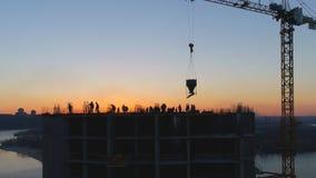 Воздушная съемка строительной площадки с кранами и работниками на заходе солнца видеоматериал