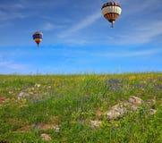 2 воздушного шара летают над полем Стоковые Изображения