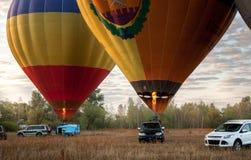 2 воздушного шара принимая в поле на восходе солнца Стоковые Изображения