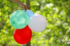Воздушные шары в саде в руках ` s девушки в саде Стоковые Фотографии RF