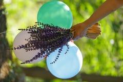 Воздушные шары и цветки в саде в руках ` s девушки в саде Стоковая Фотография RF