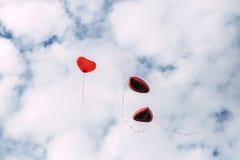 Воздушные шары сердца форменные против неба Стоковые Изображения