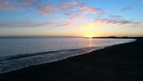 Воздушный отснятый видеоматериал захода солнца пляжа сток-видео