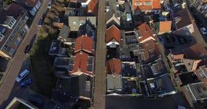 Воздушный отснятый видеоматериал над крышами домов Трутень летая над крышами и дорогой города в Голландии акции видеоматериалы