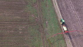 Воздушный отснятый видеоматериал трактора брызгает поля рапса с химикатами в 4K сток-видео