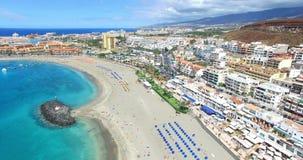 Воздушный полет над пляжем Лос Cristianos (las Америкой), Канарскими островами Тенерифе Playa de, Испанией сток-видео
