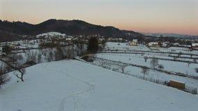 Воздушный полет над снежной деревней, камерой спуская акции видеоматериалы